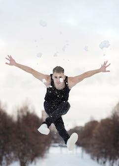 Artista hip-hop maschio che balla con la neve fuori