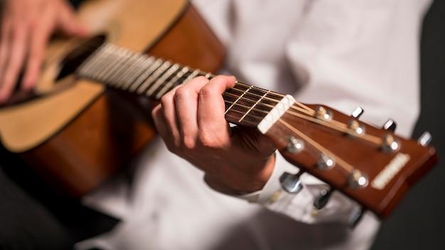Artista in camicia bianca che gioca il primo piano della chitarra