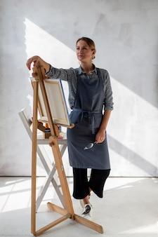 Artista in grembiule in posa con cavalletto e tela