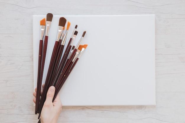 Artista irriconoscibile che tiene pennelli e carta bianca
