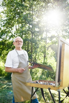 Artista maschio bello, con sguardo concepito, tenendo spazzola e immaginando l'immagine in testa in raggi di sole