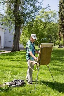 Artista maschio che lavora all'aperto nel parco o nel giardino su un cavalletto e sulla pittura del cavalletto