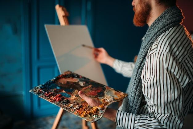 Artista maschio con tavolozza e pennello in mano davanti al cavalletto.