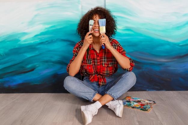 Artista sorridente della donna di colore in studio che tiene una spazzola. studente ispirato seduto sopra le sue opere d'arte.