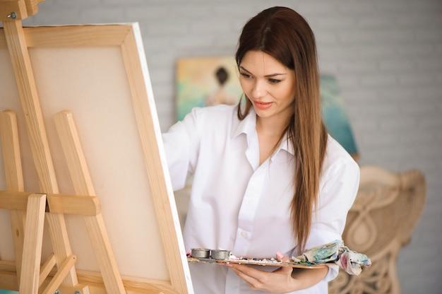 Artista sveglio della bella ragazza che dipinge un'immagine su una tela su un cavalletto. studio sfondo bianco. capelli lunghi, bruna. tenendo il pennello colorato e la tavolozza.