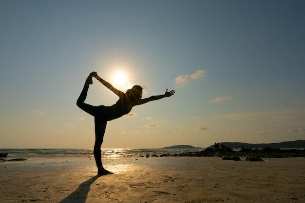 Asana dell'equilibrio di pratica della giovane donna sulla sessione di yoga di estate