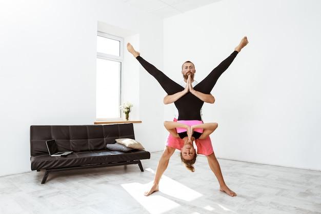 Asana di pratica di yoga del partner delle giovani belle coppie allegre a casa.