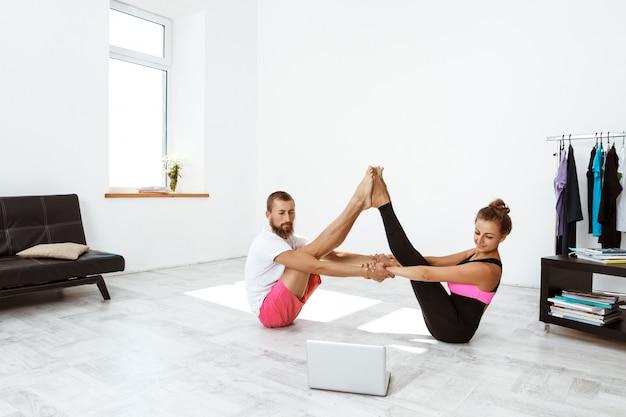 Asana di pratica di yoga delle giovani belle coppie allegre a casa. navasana.