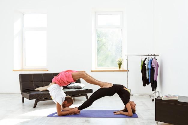Asana di pratica di yoga delle giovani belle coppie allegre a casa.