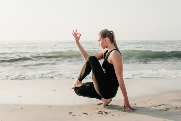 Asana di yoga di pratica della donna adatta dei giovani sulla sabbia vicino all'oceano