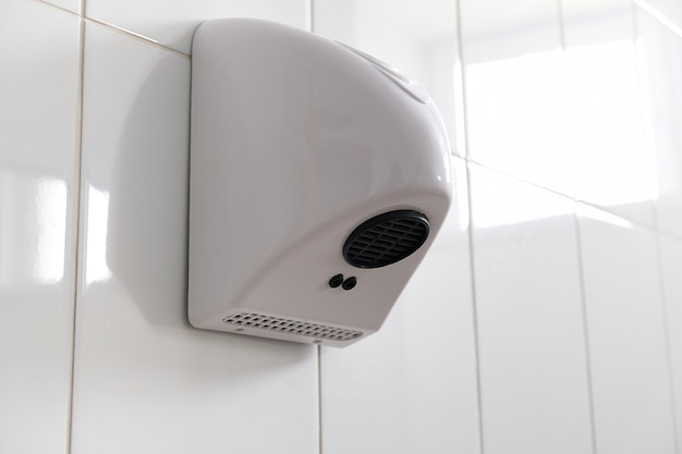 Asciugamani automatico in plastica bianca sulla parete piastrellata della toilette