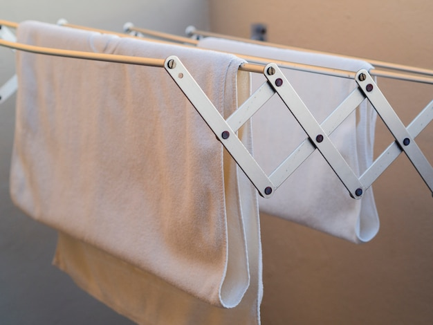 Asciugamani bianchi del primo piano che si asciugano sulla linea