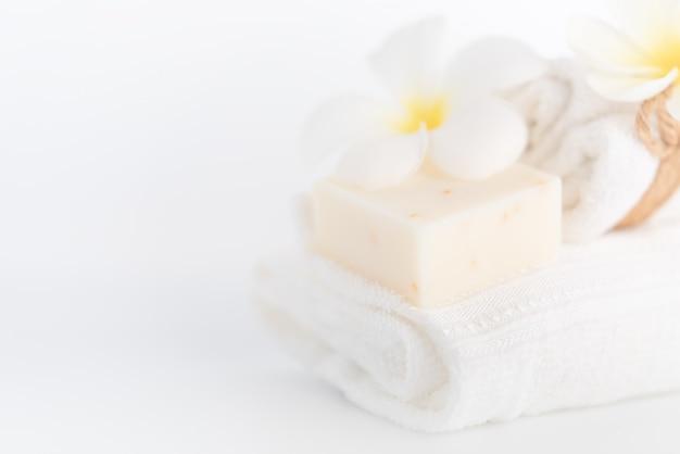 Asciugamani bianchi, sapone organico e fiore plumeria su bianco