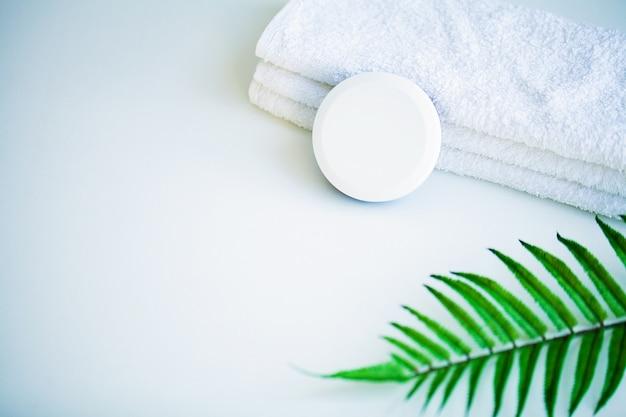 Asciugamani bianchi sulla tavola bianca con lo spazio della copia sul fondo del bagno