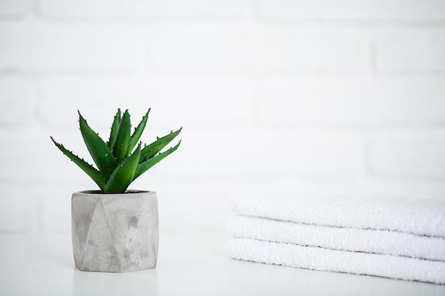 Asciugamani bianchi sulla tavola bianca con lo spazio della copia sulla stanza del bagno