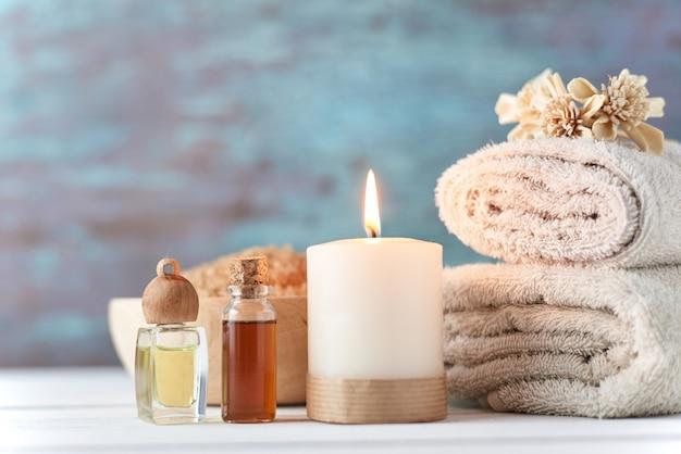 Asciugamani, candela e massaggio olio sul tavolo bianco