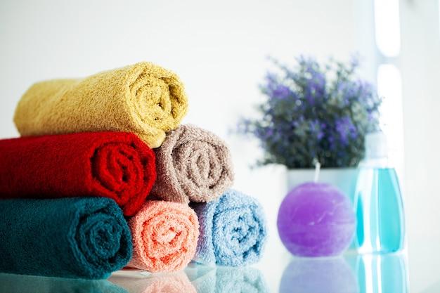 Asciugamani colorati sulla tavola bianca con lo spazio della copia sulla stanza del bagno