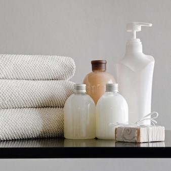 Asciugamani con shampoo, balsamo, latte doccia e sapone fatto a mano su fondo neutro. concetto di spa