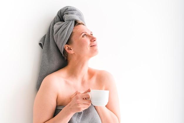 Asciugamani d'uso della donna che tengono una tazza bianca