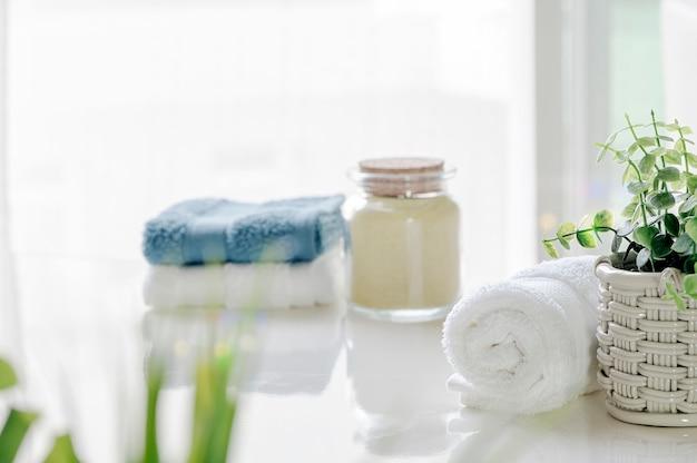 Asciugamani di bagno del modello sulla tavola bianca con la pianta da appartamento nella stanza bianca