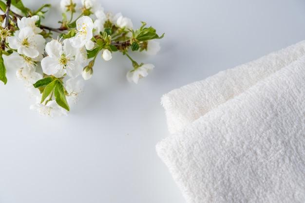 Asciugamani di bagno lanuginosi bianchi con la ciliegia di fioritura del ramo su superficie bianca. spa e concetto di cura del corpo. composizione spa. copia spazio