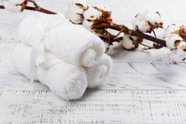 Asciugamani di cotone bianchi e ramo di cotone sul tavolo di legno