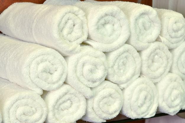 Asciugamani di cotone bianco texture di sfondo. asciugamani puliti bianchi sullo scaffale del bagno nei capelli della stazione termale o nel salone di bellezza