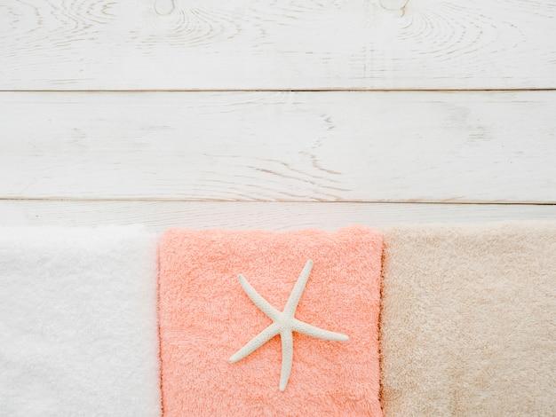 Asciugamani di disposizione piani su fondo di legno con lo spazio della copia