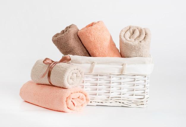 Asciugamani di spugna arrotolati di diversi colori con un nastro su uno sfondo bianco, asciugamani in un cestino bianco davanti a uno sfondo bianco