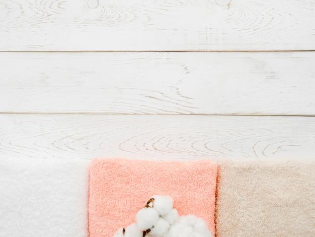 Asciugamani di vista superiore su fondo di legno con lo spazio della copia