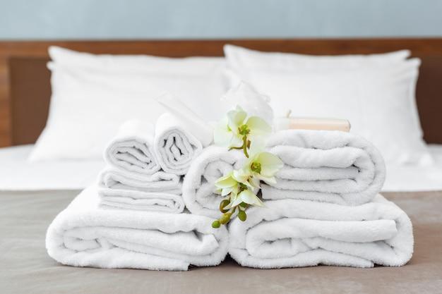 Asciugamani e fiori sul letto nella camera d'albergo