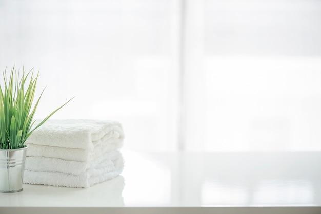 Asciugamani e houseplant sulla tabella bianca con lo spazio della copia