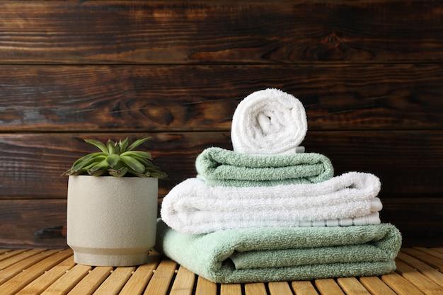 Asciugamani e pianta succulente sulla tavola di bambù su legno, spazio per testo