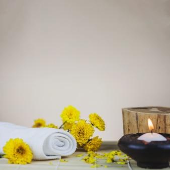 Asciugamani, fiori, tronco e candela