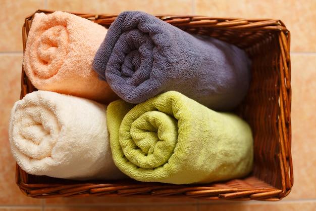 Asciugamani puliti arrotolati in un cestino sul pavimento. giorno di bucato.