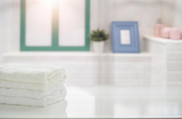 Asciugamani sul tavolo bianco in bagno con spazio di copia.