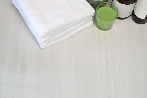 Asciugamani vista superiore con accessorio spa sul tavolo in legno e lo spazio della copia