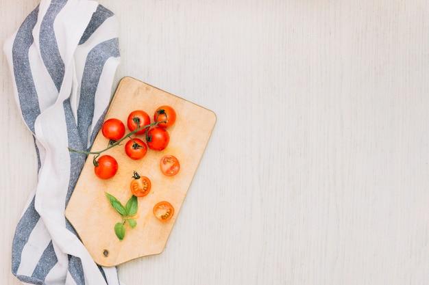 Asciugamano a righe e pomodorini sul tagliere sopra la superficie in legno