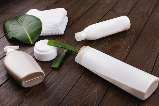 Asciugamano bianco, bottiglie di shampoo e balsamo si trovano su un tavolo con foglia verde e aloe