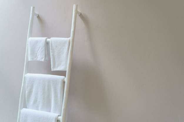 Asciugamano bianco che appende sul supporto di legno bianco delle scale.