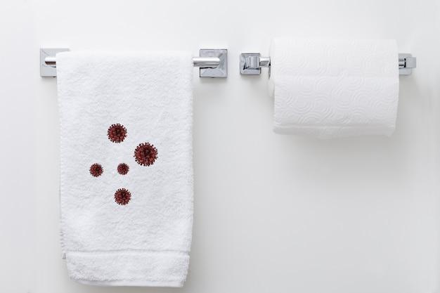 Asciugamano bianco che appende sulla parete con molte cellule di coronavirus su, concetto di epidemia