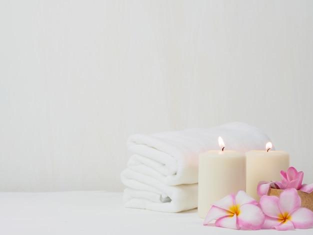Asciugamano bianco con fiore rosa rosa sul tavolo