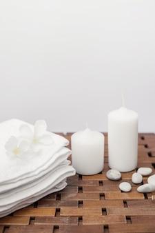 Asciugamano bianco; fiori; candele e ciottoli sulla superficie in legno