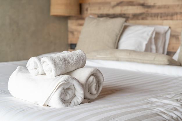 Asciugamano bianco sulla decorazione del letto in camera da letto