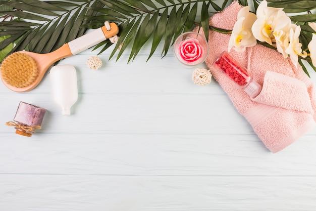 Asciugamano; bottiglia di sale; spazzola; fiori e foglie su fondo in legno