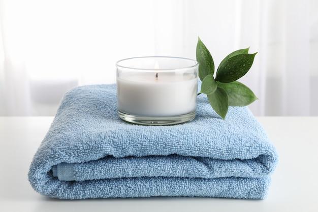 Asciugamano, candela e ruscus su bianco, copia spazio. terme