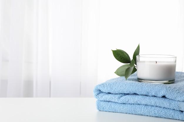 Asciugamano, candela e ruscus su fondo bianco, spazio della copia. terme
