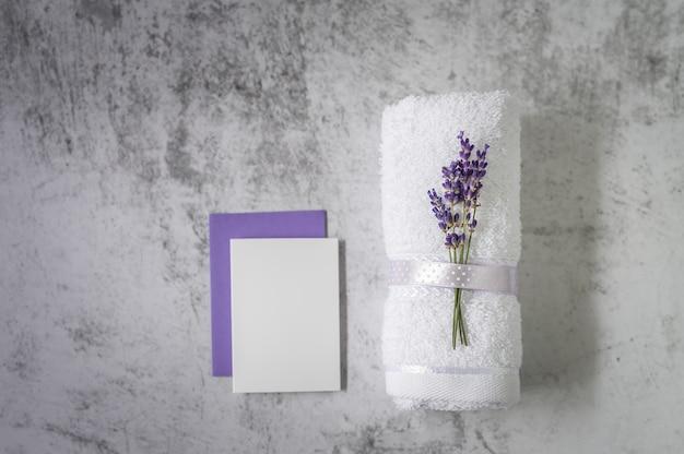 Asciugamano da bagno contorto con lavanda e cartoncino bianco su grigio chiaro. concetto spa.
