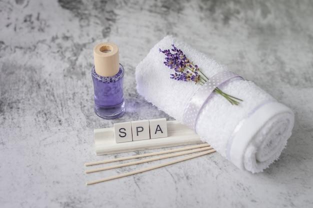 Asciugamano da bagno contorto con lavanda e ortografia di lettere in legno