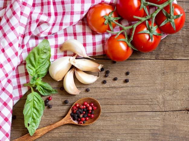 Asciugamano dei pomodori, della menta, dell'aglio, del pepe e di piatto su una vista di legno del piano d'appoggio